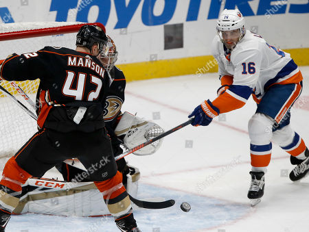 Anaheim Ducks goaltender John Gibson, center, stops a shot by New York Islanders left wing Andrew Ladd, right, wit defenseman Josh Manson defending during the third period of an NHL hockey game in Anaheim, Calif., . The Ducks won 4-1