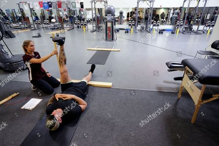 Former NFL football player Nick McDonald raises his leg as he works with Cienna Collins during a range of motion evaluation at Exos in Carlsbad, Calif. McDonald played for the Green Bay Packers, New England Patriots, San Diego Chargers, and Cleveland Browns during his time playing football in the NFL