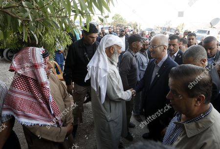 Palestinian Prime Minister Rami Hamdallah (C-R) visits the Palestinian Bedouin village of Khan al-Ahmar, located between the West Bank city of Jericho and Jerusalem near the Israeli settlement of Maale Adumim, 18 October 2018. Khan al-Ahmar is a Bedouin community where some 180 people live in shacks, that Israeli authorities claim were built without obtaining permits. Israeli authorities plan to demolish the shacks after the Israeli High Court of Justice rejected petitions filed by Khan al-Ahmar residents against their evacuation.