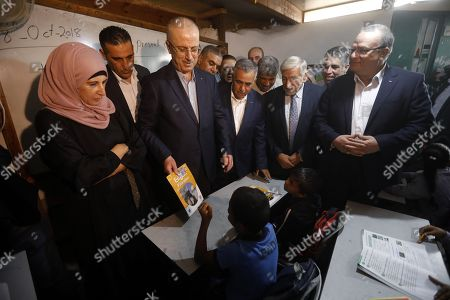 Palestinian Prime Minister Rami Hamdallah (C) visits a school in the Palestinian Bedouin village of Khan al-Ahmar, located between the West Bank city of Jericho and Jerusalem near the Israeli settlement of Maale Adumim, 18 October 2018. Khan al-Ahmar is a Bedouin community where some 180 people live in shacks, that Israeli authorities claim were built without obtaining permits. Israeli authorities plan to demolish the shacks after the Israeli High Court of Justice rejected petitions filed by Khan al-Ahmar residents against their evacuation.