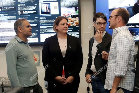 Samidh Chakrabarti, Director of Elections and Civic Engagement, from left, listens with Katie Harbath, Global Politics and Government Outreach Director and Nathaniel Gleicher, Head of Cybersecurity Policy as Tom Reynolds, Policy Communications, speaks to them during a demonstration in the war room, where Facebook monitors election related content on the platform, in Menlo Park, Calif