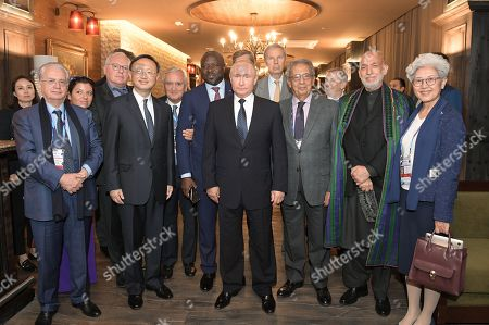 (front row, L-R) State Hermitage Museum general director Mikhail Piotrovsky, Chinese Director of the Central Foreign Affairs Commission Office Yang Jiechi, Russian President Russia Vladimir Putin, Egyptian diplomat and politician Amr Moussa, former President of the Islamic Republic of Afghanistan Hamid Karzai, Chinese politician and diplomat Fu Ying, (back row L-R) unidentified participant, RT television channel and Rossiya Segodnya Editor-in-Chief Margarita Simonyan , co-director of the Center for Governance and Public Policy at Carleton University Piotr Dutkiewicz, French politician and ex-Prime Minister Jean-Pierre Raffarin, Executive Secretary of the Preparatory Commission for the Comprehensive Nuclear-Test-Ban Treaty Organisation (CTBTO) Lassina Zerbo, former French diplomat and former UN Under-Secretary-General Jean-Marie Guehenno and Council Chairman of the Foundation for Development and Support of the Valdai Discussion Club Andrei Bystritsky pose for a picture on the sidelines  of the 15th anniversary meeting of the Valdai International Discussion Club in the Black sea resort of Sochi, Russia, 18 October 2018.