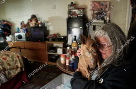 Melissa Smith holds her dog Bella in her room at a weekly rental motel in Reno, Nev. Smith has lived in weekly and monthly rental motels for about two years