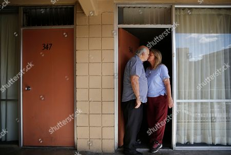"Dave Frazier, left, kisses Dawn Robinson at the door of the room where they live at the Fireside Inn motel in Reno, Nev. ""We're not worried with keeping up with the Joneses,"" said Frazier, ""We just want to keep a roof over our head"