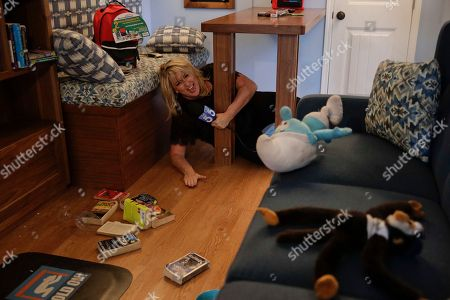 """TV reporter Wendy Burch takes cover under a table in a Big Shaker simulating a 6.8 magnitude earthquake, in Los Angeles. Millions of people around the world are practicing the basic earthquake safety skill of """"drop, cover and hold on."""" Thursday marks the 10th anniversary of the """"Great ShakeOut"""" earthquake drills that originated in Southern California"""