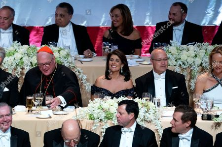 Stock Image of Keynote speaker Ambassador to the United Nations Nikki Haley, center, shares a light moment as she attends the 73rd Annual Alfred E. Smith Memorial Foundation Dinner, in New York. Left is Archbishop of New York Cardinal Timothy Dolan, and right is Michael Haley, husband of Nikki Haley
