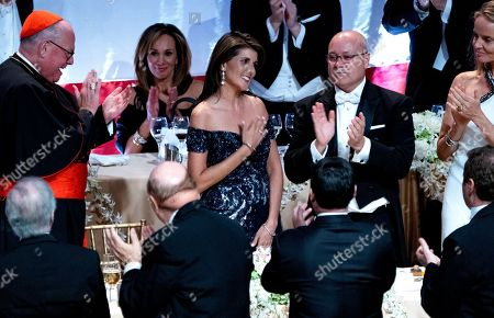 Ambassador to the United Nations Nikki Haley, center, acknowledges applause after her keynote address at the 73rd Annual Alfred E. Smith Memorial Foundation Dinner, in New York. Far left is Archbishop of New York Cardinal Timothy Dolan, and right is Michael Haley, husband of Nikki Haley