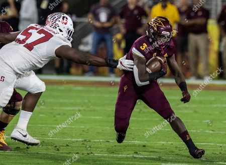 Arizona State's Eno Benjamin slips past Stanford's Michael Williams during the first half of an NCAA college football game, in Tempe, Ariz