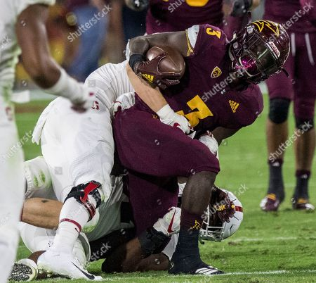 Arizona State's Eno Benjamin gets tackled by Stanford's Michael Williams during the first half of an NCAA college football game, in Tempe, Ariz