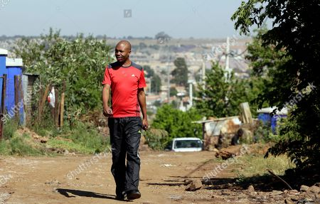 """Stock Picture of Somsy Matso, a community leader in the local housing fight, walks along a street at Winnie Mandela Informal Settlement in Tembisa, of east of Johannesburg, South Africa, . As South Africa's passionate debate over land redistribution grows, one city outside Johannesburg is preparing what the mayor calls a """"test case"""" for the nation _ the seizure of hundreds of acres of land from private owners, without paying for it, to build low-cost housing"""