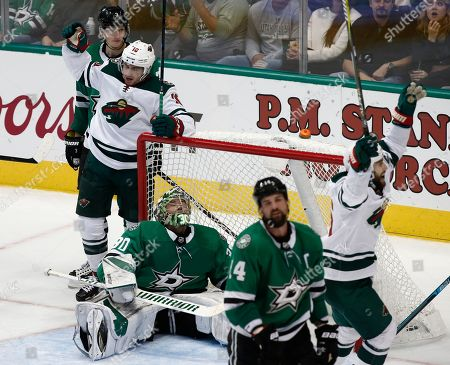 Minnesota Wild wing Matt Read, second from left, and wing Jason Zucker, right, celebrate after defenseman Matt Dumba (not shown) scored a goal as Dallas Stars goalie Ben Bishop, center, wing Jamie Benn (14) and defenseman John Klingberg, left, are nearby during the third period of an NHL hockey game, in Dallas