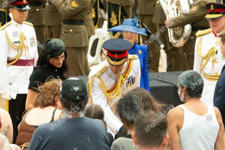 Britain's Prince Harry, center, and his wife Meghan Duchess of Sussex Megan, left, speak to indigenous Australians while attending the opening of the enhanced ANZAC Memorial in Sydney,. The Duke and Duchess are on a tour to Australia, Fiji, Tonga and New Zealand