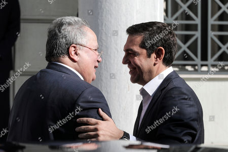Greece's Prime Minister and newly appointed Foreign Minister Alexis Tsipras, right, shakes hands with outgoing Foreign Minister Nikos Kotzias during a ceremony in Athens, . Kotzias resigned Wednesday following a disagreement with the defense minister over the handling of a deal for Greece to drop its objections to neighboring Macedonia joining NATO if the small country's name is changed
