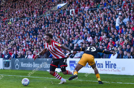 Stock Picture of Reggie Zippy Lambe of Cambridge United pulls back Bruno Andrade of Lincoln City in front of a packed house at Sincil Bank and the Lincolnshire Co-op Stand