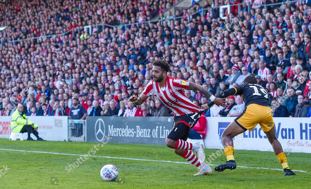 Stock Image of Reggie Zippy Lambe of Cambridge United pulls back Bruno Andrade of Lincoln City in front of a packed house at Sincil Bank and the Lincolnshire Co-op Stand