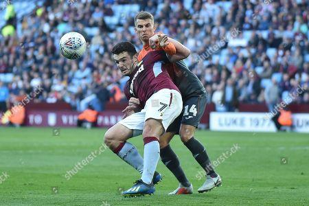Swansea City midfielder Tom Carroll (14) hauls down Aston Villa midfielder John McGinn (7) in the box the EFL Sky Bet Championship match between Aston Villa and Swansea City at Villa Park, Birmingham