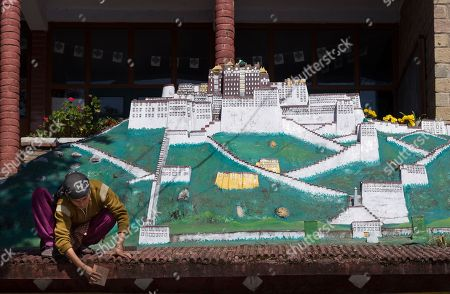 A woman cleans moss off a wall in front of a plaster replica of the Potala Palace, the traditional seat of Tibetan political and spiritual leadership and residence of Dalai Lamas since the 17th century in Lhasa, in Dharmsala, India, . The last official resident of the palace was Tenzin Gyatso, the 14th Dalai Lama, who fled to exile to India in 1959
