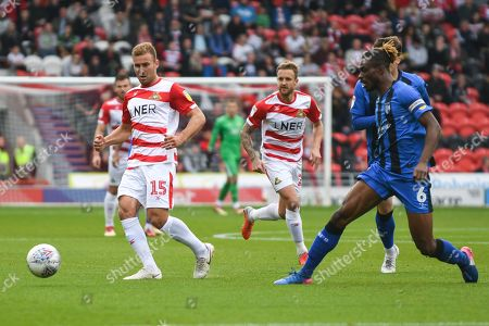 Herbie Kane of Doncaster Rovers (15) passes the ball forward with Gabriel Zakuani of Gillingham (6) defending during the EFL Sky Bet League 1 match between Doncaster Rovers and Gillingham at the Keepmoat Stadium, Doncaster