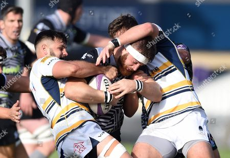 Rhodri Jones of Ospreys is tackled by Ethan Waller and Matti Williams of Worcester Warriors.