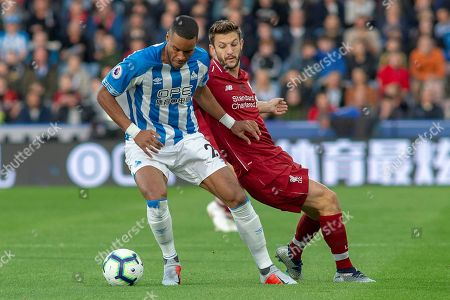 Collin Quaner of Huddersfield Town battles with Liverpool midfielder Adam Lallana during the Premier League match between Huddersfield Town and Liverpool at the John Smiths Stadium, Huddersfield