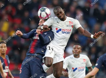 PSG's Marquinhos, left, and Amiens' Moussa Konate jump for the ball during the French League One soccer match between Paris-Saint-Germain and Amiens at the Parc des Princes stadium in Paris, France