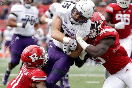 Northwestern running back Isaiah Bowser, center, is tackled by Rutgers defensive back Isaiah Wharton, left, and linebacker Trevor Morris during the first half of an NCAA college football game, in Piscataway, N.J