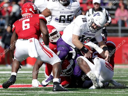 Northwestern quarterback Clayton Thorson, center, is stripped of the football by Rutgers linebacker Trevor Morris, right, during the second half of an NCAA college football game, in Piscataway, N.J. Rutgers recovered the fumble on the play. Northwestern won 18-15