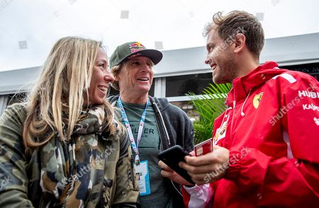 Stock Picture of German Formula One driver Sebastian Vettel (R) of Scuderia Ferrari and US surfing legend Robby Naish (C) prior to the third practice session of the United States Formula One Grand Prix at the Circuit of the Americas, in Austin, Texas, USA, 20 October 2018. The United States Formula One Grand Prix takes place on 21 October 2018.