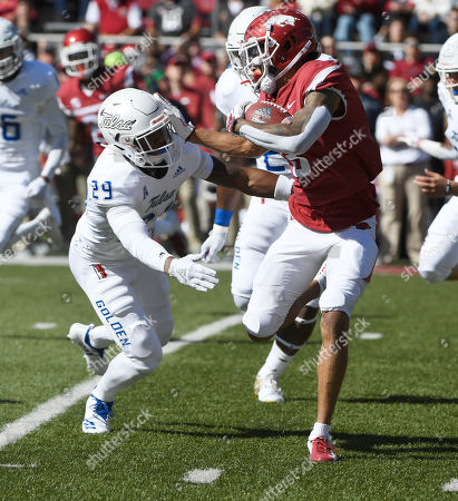 Arkansas kick returner Deon Stewart, right, tries to get past Tulsa defender Brandon Johnson as he returns a kick in the first half of an NCAA college football game, in Fayetteville, Ark