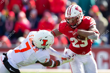 Wisconsin Badgers running back Jonathan Taylor #23 stiff arms Illinois Fighting Illini defensive back Stanley Green #7 during the NCAA Football game between the Illinois Fighting Illini and the Wisconsin Badgers at Camp Randall Stadium in Madison, WI. Wisconsin defeated Illinois 49-20