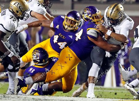 Central Florida's Darriel Mack Jr. (8) is tackled by East Carolina's Alex Turner (94) with Kendall Futrell (44) looking on during the first half of an NCAA college football game in Greenville, N.C