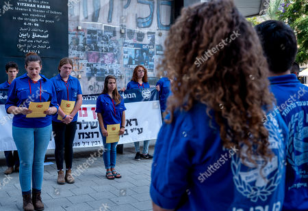 Activists of an Israeli youth organization hold a memorial vigil at the memorial in Rabin Square in Tel Aviv, Israel, 21 October 2018, honoring Israel's Prime Minister Yitzhak Rabin who was assassinated on this spot on 04 November 1995, by an ultra-Orthodox Jewish gunman. The day marks the 23rd anniversary since the assassination according to the Hebrew calendar. On the wall behind are photos and graffiti from 1995 including a phrase said by then US President Bill Clinton about his friend Rabin, 'Buddy, you are missed.'