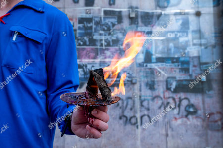 An activist of an Israeli youth organization holds a burning torch in front of the memorial in Rabin Square in Tel Aviv, Israel, 21 October 2018, during a short memorial service to Israel's Prime Minister Yitzhak Rabin who was assassinated on this spot on 04 November 1995, by an ultra-Orthodox Jewish gunman. The day marks the 23rd anniversary since the assassination according to the Hebrew calendar. On the wall behind are photos and graffiti from 1995 including a phrase said by then US President Bill Clinton about his friend Rabin, 'Buddy, you are missed.'