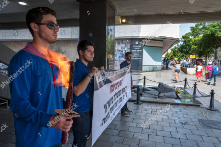 An activist of an Israeli youth organization holds a burning torch in front of the memorial in Rabin Square in Tel Aviv, Israel, 21 October 2018, during a vigil honoring Israel's Prime Minister Yitzhak Rabin who was assassinated on this spot on 04 November 1995, by an ultra-Orthodox Jewish gunman. The day marks the 23rd anniversary since the assassination according to the Hebrew calendar.