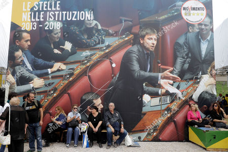 Five Stars movement supporters gather in front of a huge poster showing Five-Star movement lawmaker Alessandro Di Battista during a rally at Rome's Circus Maximus