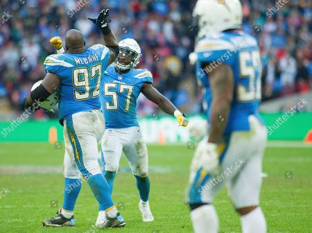 L A Chargers Defensive Linesman Issac Rochell (98) and L A Chargers Linebacker Jatavis Brown (57) celebrate the win over the Tennessee Titans