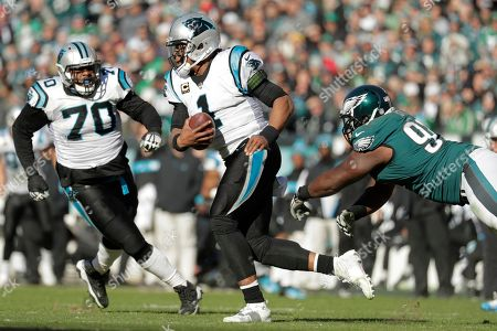 Carolina Panthers quarterback Cam Newton, center, runs with the ball by the diving attempt of Philadelphia Eagles defensive tackle Fletcher Cox, right, during the second half of an NFL football game, in Philadelphia. Panthers offensive guard Trai Turner (70) helps block on the play