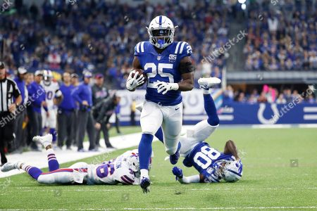 Indianapolis Colts running back Marlon Mack (25) heads for the end zone for a touchdown past the block of wide receiver Chester Rogers (80) on Buffalo Bills defensive back Dontae Johnson (36) during the first half of an NFL football game in Indianapolis