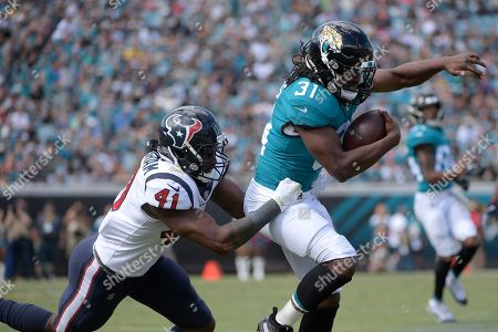 Jacksonville Jaguars running back Jamaal Charles (31) is tackled by Houston Texans linebacker Zach Cunningham (41) after catching a pass during the second half of an NFL football game, in Jacksonville, Fla. The Texans won 20-7