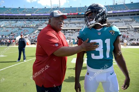 Houston Texans defensive coordinator Romeo Crennel talks with Jacksonville Jaguars running back Jamaal Charles (31) during warmups before an NFL football game, in Jacksonville, Fla
