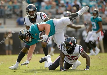 Jacksonville Jaguars running back Tommy Bohanon, center, is stopped by Houston Texans strong safety Kareem Jackson, lower right, and linebacker Zach Cunningham (41) during the second half of an NFL football game, in Jacksonville, Fla