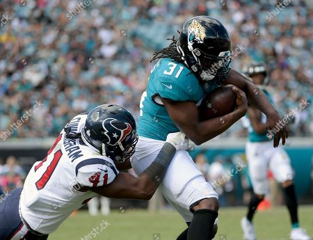 Stock Image of Jacksonville Jaguars running back Jamaal Charles (31) is stopped after a reception by Houston Texans linebacker Zach Cunningham (41) during the second half of an NFL football game, in Jacksonville, Fla