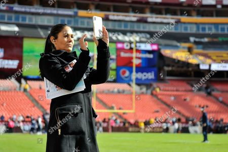 CBS sportscaster Tracy Wolfson takes picture of the field prior to an NFL football game between the Dallas Cowboys and Washington Redskins, in Landover, Md