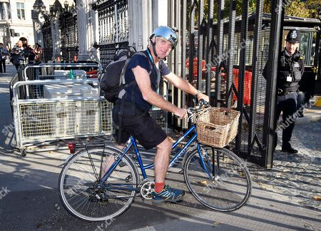 Conservative MP Desmond Swayne arrives at the houses of Parliament riding a bike, wearing shorts and a silver helmet.