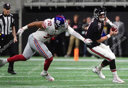 New York Giants defensive end Kerry Wynn (72) works to sack Atlanta Falcons quarterback Matt Ryan (2) during the first half of an NFL football game, in Atlanta