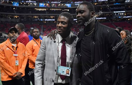 Former NFL players Warrick Dunn, left and Michael Vick stand on the sidelines before the first half of an NFL football game between the Atlanta Falcons and the New York Giants, in Atlanta