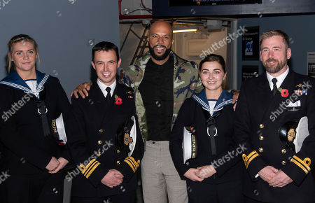 Common, center, poses with sailors from the Royal Navy's HMS Queen Elizabeth II