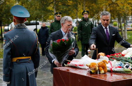 U.S. National Security Adviser John Bolton, center, and U.S. Ambassador to Russia Jon Huntsman, right, attend a flower-laying ceremony at a memorial in memory of the victims of last week's attack on a vocational college in Kerch, on the Crimean peninsula, in the Alexander Garden near the Kremlin, in Moscow, Russia, . U.S. President Donald Trump's national security adviser Bolton struck a conciliatory note Tuesday in talks in Moscow, just days after Trump vowed to pull out of a key arms control treaty with Russia