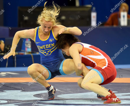 Jong Myong-suk (red) of North Korea in action against Sofia Mattsson (blue) of Sweden in their repechage bout of the women's 55kg category at the Wrestling World Championships in Budapest, Hungary, 23 October 2018.