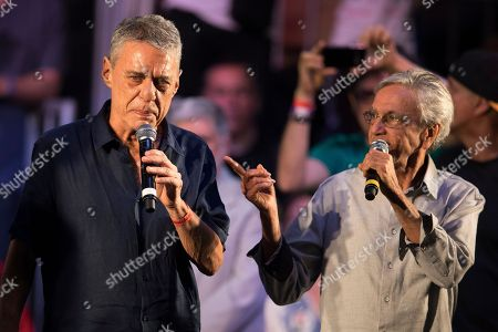 Brazilian singers Chico Buarque, and Caetano Veloso, right, speak during a campaign event with popular Brazilian artists and musicians in support Fernando Haddad, Brazil's presidential candidate for the Workers Party in Rio de Janeiro, Brazil, . Haddad will face Jair Bolsonaro, a far-right congressman, in a presidential runoff on Sunday